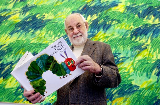 Author Eric Carle stands in front of a bright green, yellow, and blue wall holding his book, THE VERY HUNGRY CATERPILLAR
